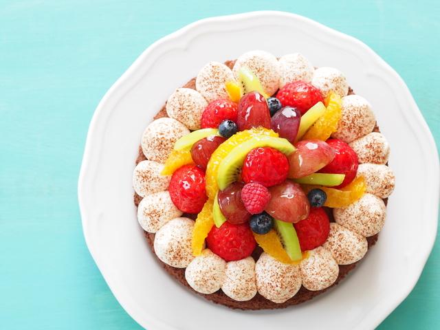 イメージ画像:水色のテーブルの上に置かれたフルーツがたくさんのったホールケーキを真上から見た写真