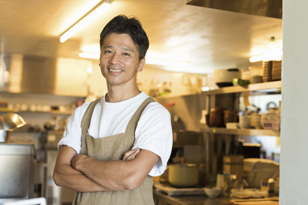 イメージ画像:レストランの店内で、白いTシャルにベージュのエプロン姿で腕組みをしながら笑っている男性料理人