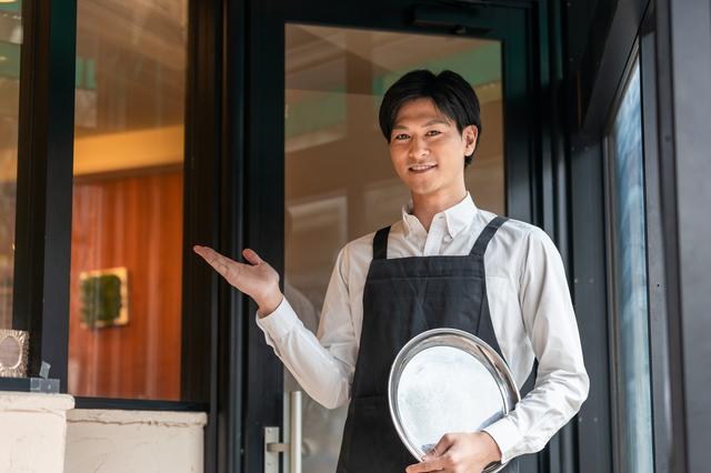イメージ画像:レストランの店内で白いシャツに黒いエプロンをかけた男性サービススタッフが案内している写真