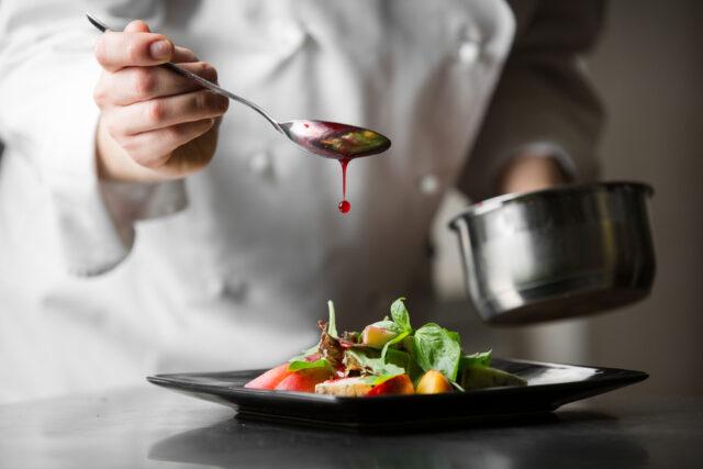 イメージ写真:コック服の料理人がお皿の上に盛り付けられた野菜の上にソースをかけている