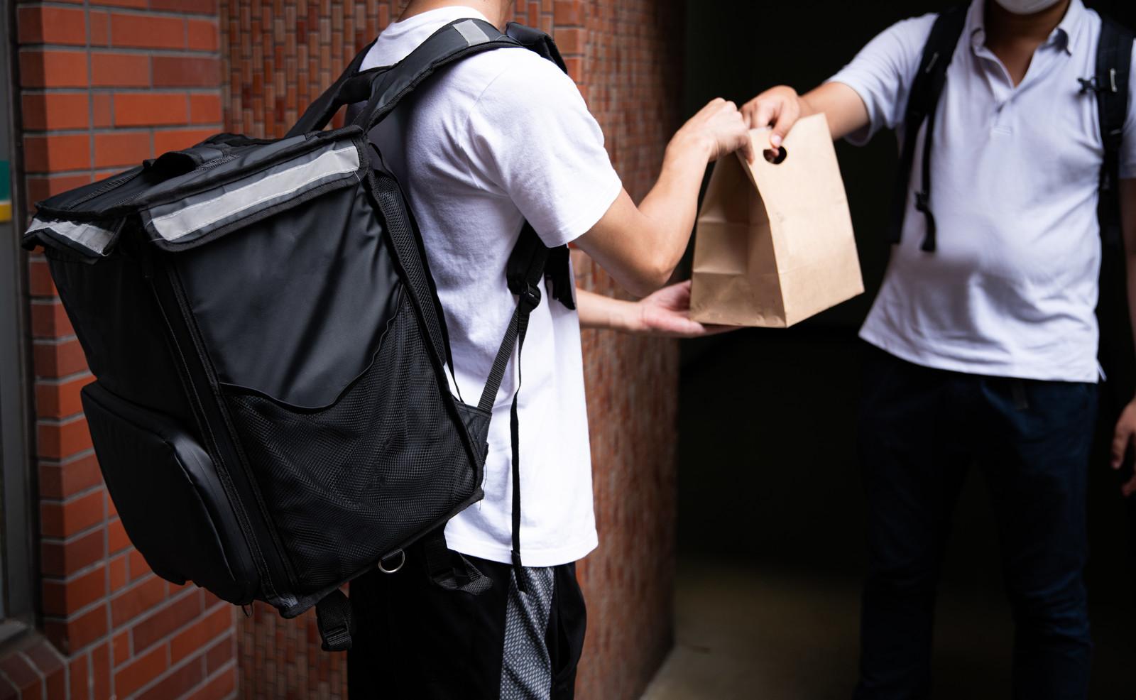 イメージ画像:玄関先で配達員より注文した商品を受け取る風景