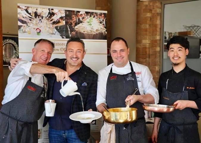吉川さんのFacebookより、4名の男性が料理を持っている写真