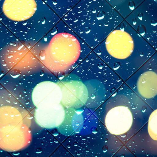 イメージ写真:雨粒に濡れる窓ガラスの向こうにネオンが輝く写真