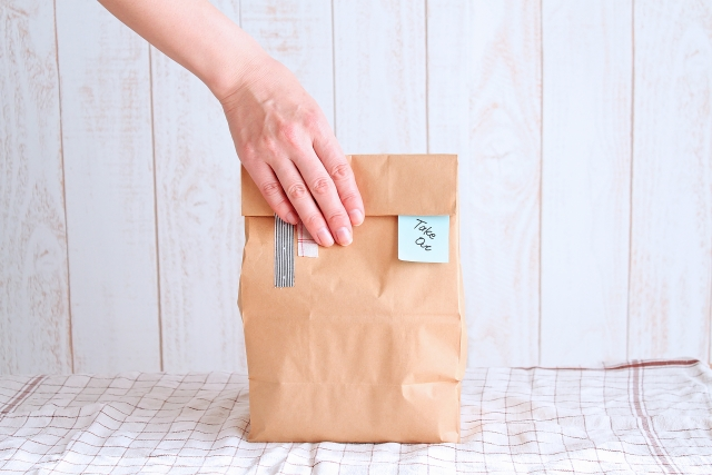 テイクアウト商品が入ったA4サイズぐらいの紙袋を片手で持ち上げようとしている