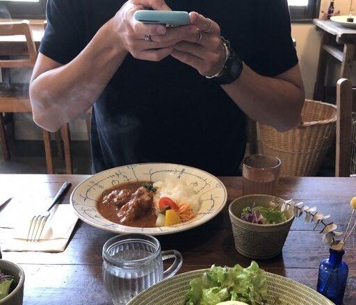 イメージ:レストランで自分が注文したカレーライスをスマホのカメラで撮影する男性