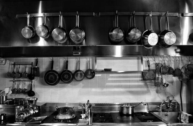 イメージ:無機質な雰囲気の厨房の写真。大小さまざまなシルバーのお鍋やフライパンが並んでいる