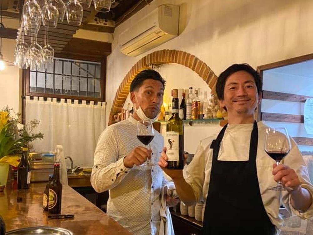 お店のカウンターでワインを片手にスタッフと笑顔の本間さんの写真
