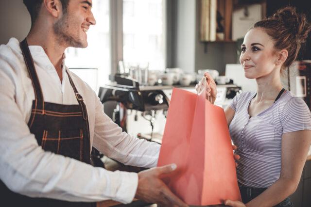 イメージ:男性スタッフよりテイクアウト商品を受け取る女性客
