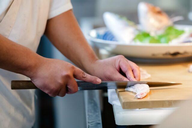 イメージ:料理人の手元。鯛の刺身を引いている