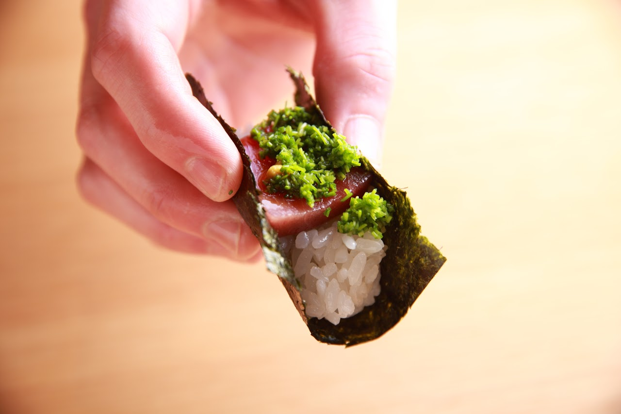マグロの手巻き寿司 黄身醤油がけを手に持っている写真
