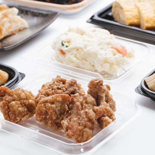 イメージ:テーブルの上に並べられた、唐揚げやポテトサラダなどのお惣菜