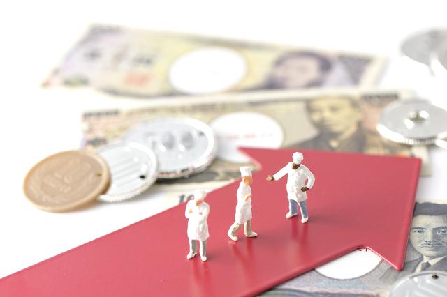 イメージ:紙幣と硬貨、赤い矢印のプレート上にはコックの人形。お金を管理して業績を伸ばすイメージ写真