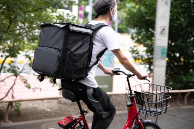 イメージ:フードデリバリーのバッグを背中に背負い、自転車に乗ってデリバリーをするマスク姿の男性