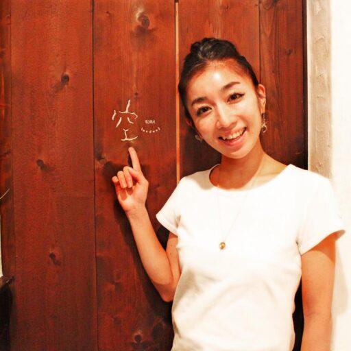 壁に書かれた店名の「空」という字を指さす笑顔の荒川さんの写真