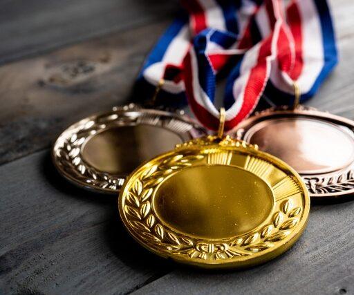 イメージ:黒っぽい木のテーブルの上に重ねるように並べられたぴかぴかの金・銀・銅メダル