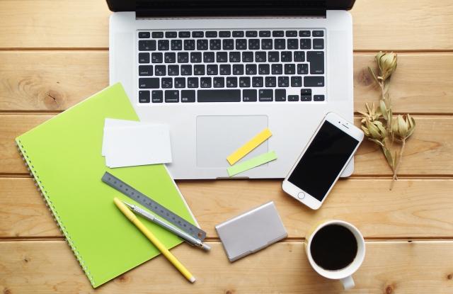 イメージ:木のデスクの上に散らばったさまざまのツール。ノートPCやスマートフォン、メモ帳、さまざまなペンなど