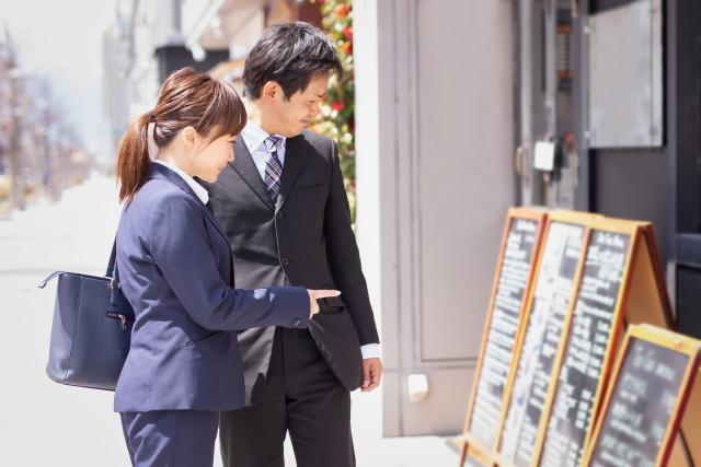 イメージ:ランチで何を食べようか迷っているスーツ姿の男女。店の入り口に掲示された黒板でメニューを見ている