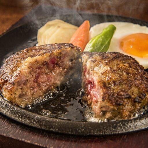 イメージ写真:鉄板の上に乗った熱々のハンバーグが半分に割られ肉汁が流れ出している