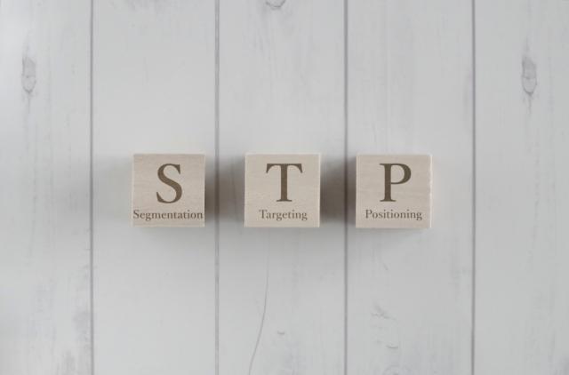 イメージ:白いテーブルの上に並べられた3個の木製の立方体ブロック。それぞれ「S」「T」「P」の文字が書かれている。