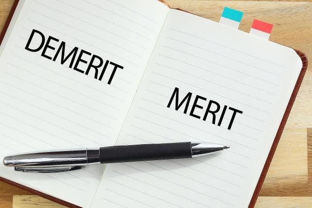 メリットとデメリットのイメージ写真。開かれたノートの右側のページにはアルファベットで「MERIT」の大きな文字。左側のページに「DEMERIT」の文字が書かれ、ボールペンが置かれている。