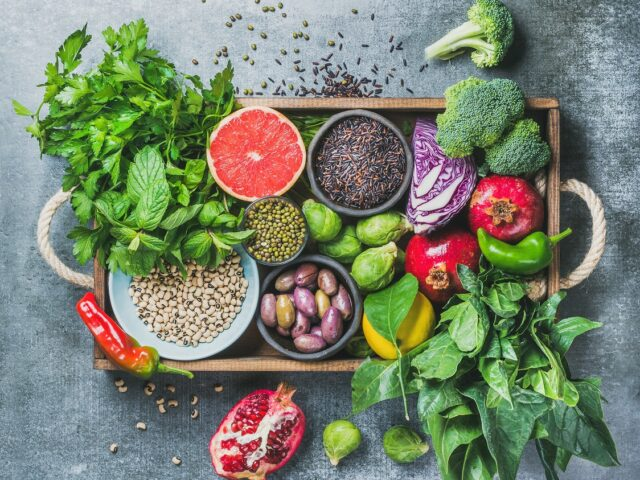 イメージ:無機質なグレーのテーブルの上に雑多にちりばめられた野菜や果物、香辛料など