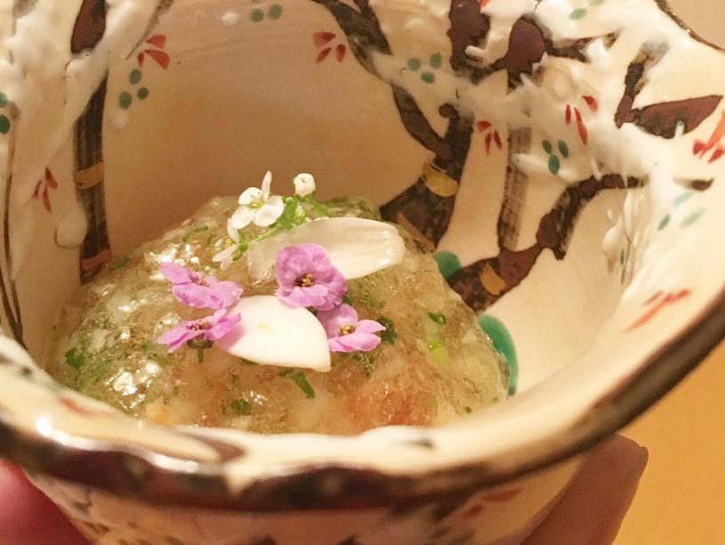 陶器の食器に花の乗ったジュレのような料理の写真