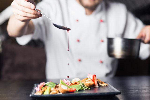 イメージ:盛り付けられたサラダにソースをかける瞬間。スプーンからソースのしずくが垂れている。