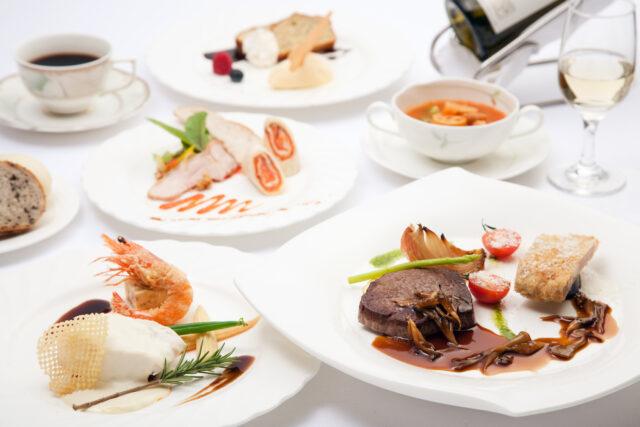 イメージ:白いテーブルの上にならべられたフレンチのコース料理。