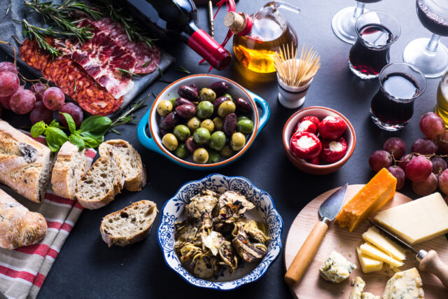 イメージ:黒いテーブルの上に並べられたパンや、オリーブ、サラミ、ワインなど