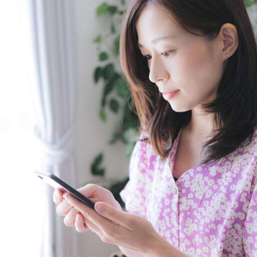 イメージ:カフェの店内でピンク色の服を着た女性がスマートフォンを使ってセルフオーダーを行っている様子