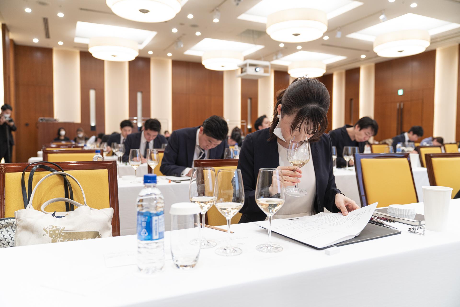 広い会場内で参加者がワインテイスティングをしている様子の写真
