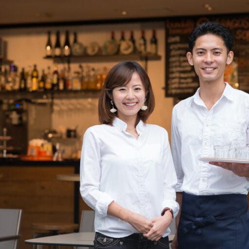 イメージ:カフェレストランのお店の前で、こちらを向いて笑顔で並んでいる白いシャツを着た男女のスタッフ