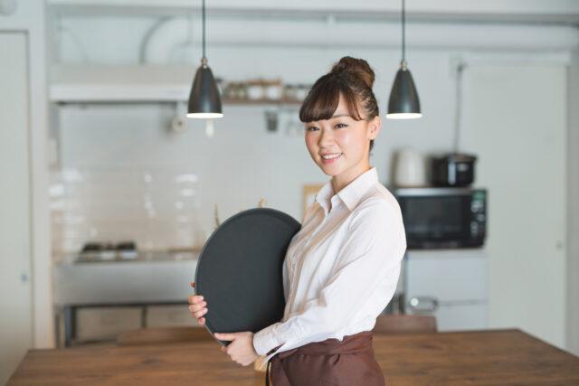 接客のイメージ写真。カフェの店内で、白いシャツを着た女性スタッフが、黒いトレンチ(お盆)を持ってこちらを向いて笑っている。