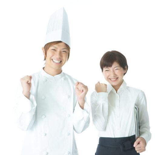 イメージ:コックコートとイメージ:コックコートとコック帽をかぶった20代前半ほどの男の子と、白いシャツを着た同年代のショートカットの女性が二人並んでガッツポーズをとっている