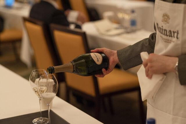 ワイングラスにシャンパンを注いでいる手もとの様子の写真