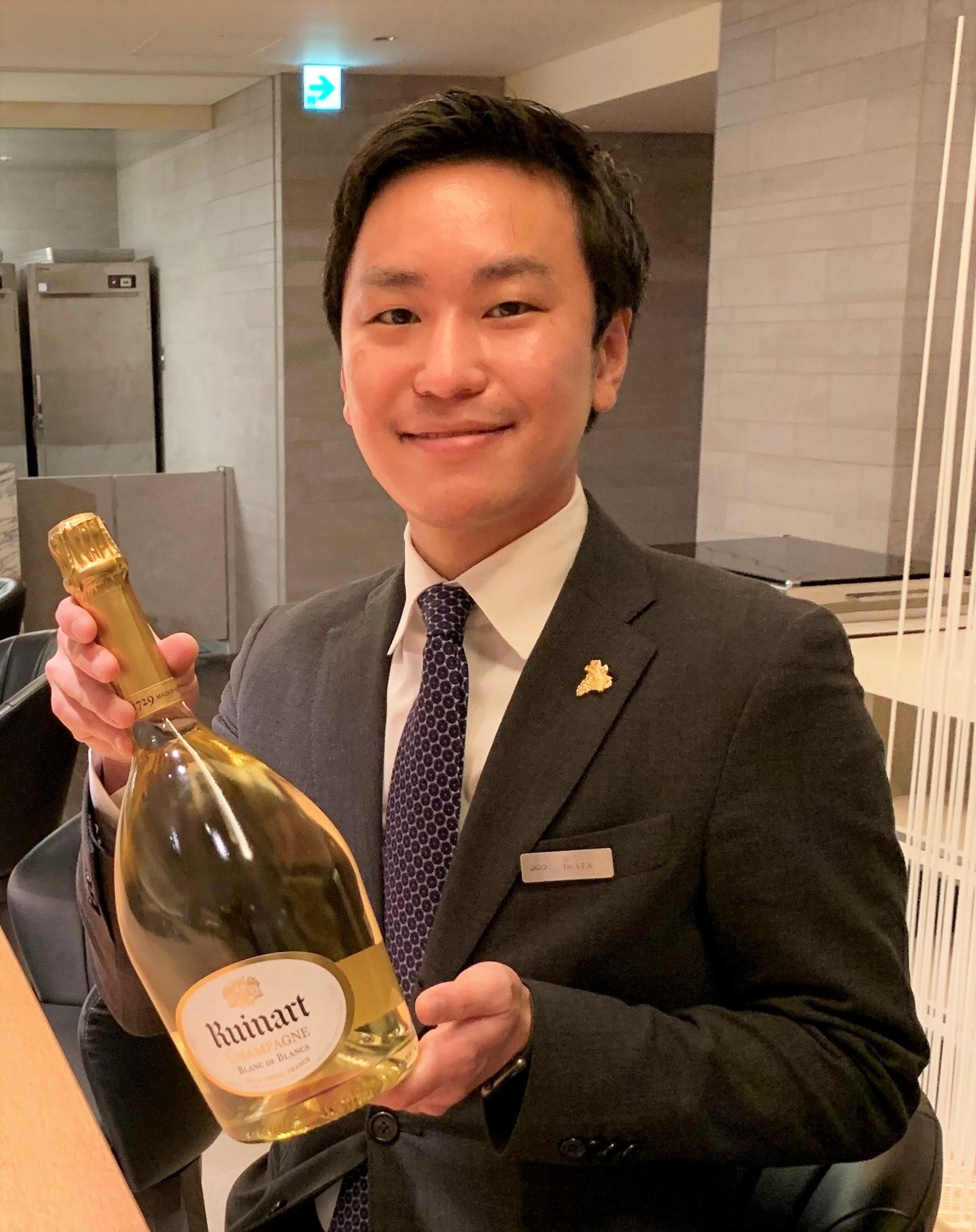 ルイナールのボトルを持つ岩田さんの写真
