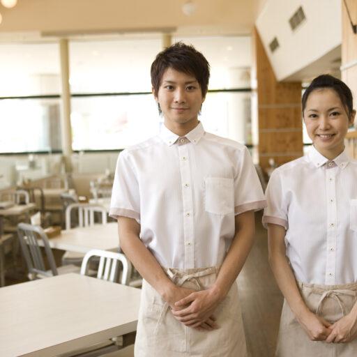 イメージ写真:木のぬくもり感じるカフェレストラン店内で、男女のスタッフが2名並んでこちらに向かって立っている
