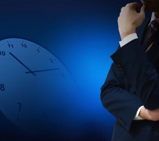 時間管理に悩むイメージ写真。暗めの背景に時計の文字盤。手前にはスーツの男性が腕組みをして悩んでいる