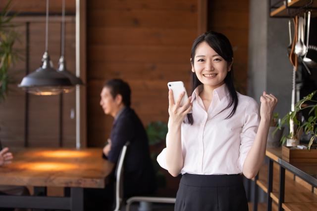 「電話対応うまくできた!」のイメージ写真:レストランの店内で電話を持ってガッツポーズをとる女性スタッフ