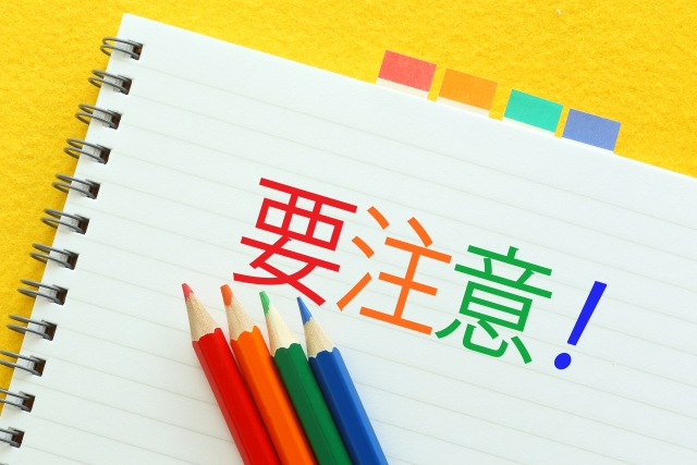 「要注意」イメージ。リングノートに赤や黄色、緑の字で大きく書かれた「要注意!」の文字。その片隅にはそれらの色の色鉛筆が並んでいる