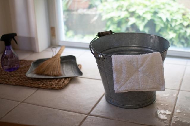 掃除のイメージ写真:窓際に置かれた掃除用具。バケツには白い雑巾がかけられ、その脇にはちりとりとほうき、洗剤が入ったスプレーボトル