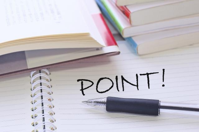 「POINT」のイメージ写真。机の上に開いて重なる本とリングノート。ノートには黒字のボールペンで「POINT!」と書かれている