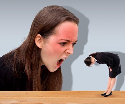 クレームのイメージ写真:真っ赤な顔で起こっている外国人女性と右側には小さくなった謝罪する女性