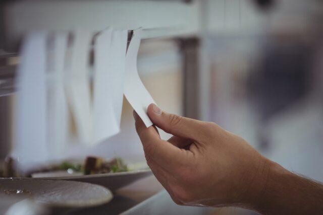 イメージ写真:厨房の棚に貼られたオーダーを1つずつ処理している風景。貼られたメモを手にとっている様子