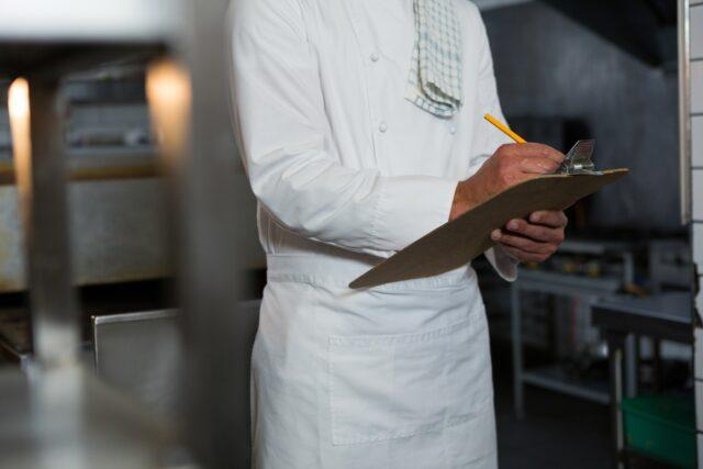 イメージ写真:コックコートを着た料理人がバインダーを手にチェックしている様子