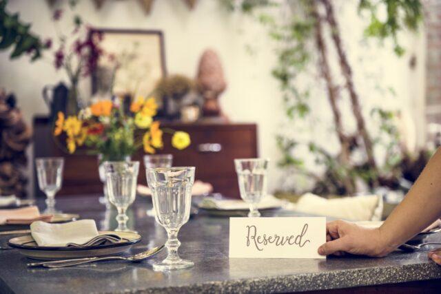 予約席のイメージ写真:アンティークな家具に囲まれたレストランのテーブルの上に複数のグラスとともに筆記体で「reserved」と書かれた札が置かれている