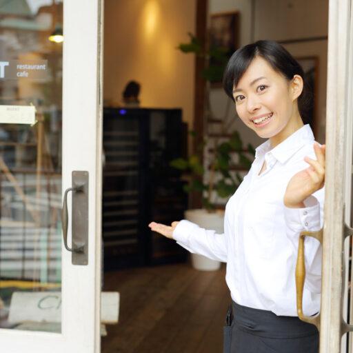 イメージ:カフェの入り口で白い枠に囲まれたガラスの扉を開け、店内に笑顔で誘導する女性スタッフ