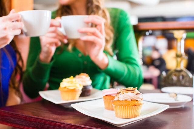 イメージ写真:カフェの店内でくつろぐ女性客。テーブルの上にはカップケーキ、手にはマグカップを持って談笑している