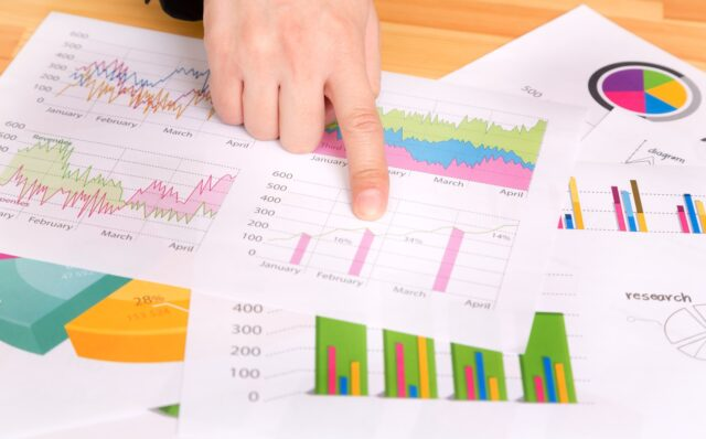 イメージ写真:机の上にちりばめられたさまざまなグラフや数値が書かれた資料。その中のグラフの一つを指さしており、打合せしている風景
