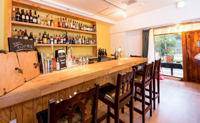 イメージ:木のカウンターがあるカフェバー。後ろの棚にはたくさんのお酒のボトルが並ぶ。
